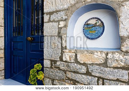 Entrance of traditional stone house, decorated with painted plate in the village of Trikeri, Thessaly, Greece