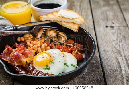 Full english breakfast - eggs, bacon, beans, toast, coffee and juice, rustic wood background
