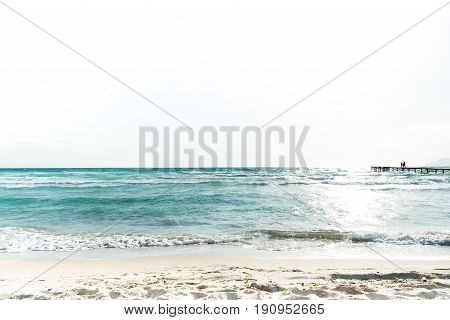 View over the Mediterranean ocean and a pier in silhoutte with people on