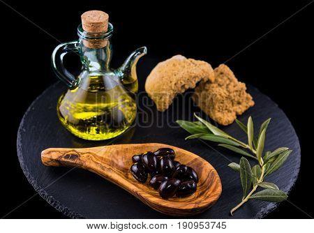 Black olives, bottle of olive oil, rusk and olive branch on black dish