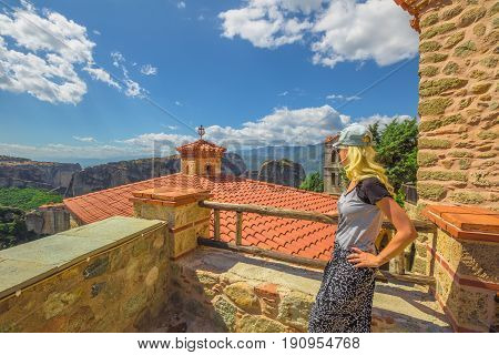 Female blonde tourist looking panorama from St. Nicholas Anapafsas Monastery in Meteora, Peloponnese, Thessaly, Greece. Tourism and travel in Europe. Caucasian woman traveler in scenic destinations.