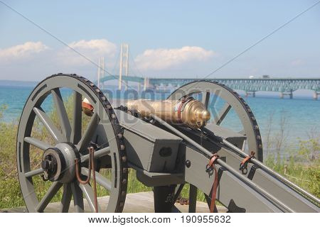 Cannon on the shores of the Straits of Mackinac, with the Mackinac Bridge in the background