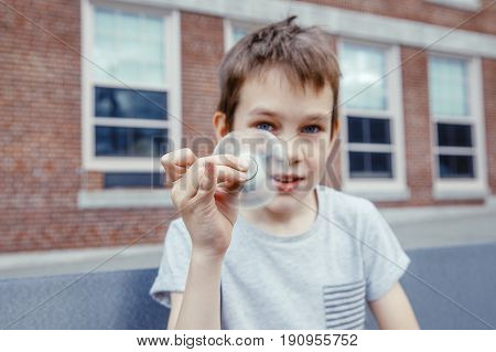 boy looking at a spinning fidget spinner. kid playing with a spinner. closeup