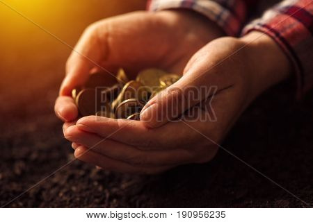 Farmer with handful of coins over soil land making money and gaining profit in agriculture