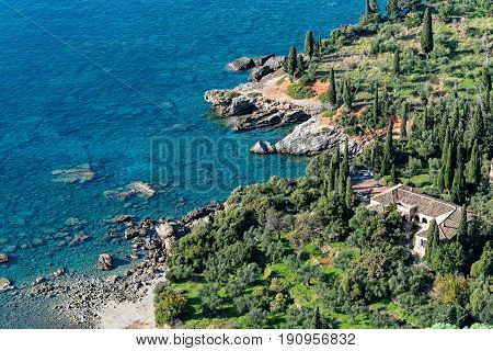 Typical mediterranean landscape with traditional house, olive trees, cypresses and blue sea in Peloponnese, Greece