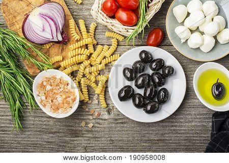 Healthy comfort food: ingredients for cooking pasta, salads, olives, sweet onions, mozzarella cheese, olive oil, juicy tomatoes on a plain wooden background. From the top view. The Mediterranean diet.