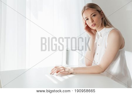 Image of serious blonde lady sitting indoors near water jug dressed in white dress. Looking at camera.