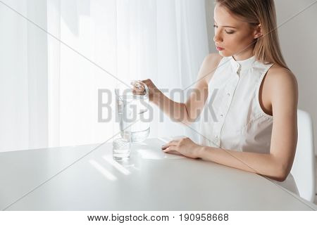 Picture of serious blonde lady sitting indoors near water jug dressed in white dress. Looking aside.