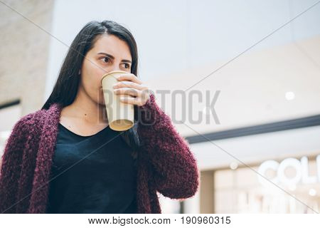 Young woman in jeans with smart phone and cup of coffee standing near cafe