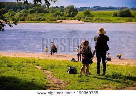 Polenovo, Tula region, Russia - June 12, 2017 - Beautiful summer beach on the river Oka coast with walking people. Drawing woman and little girls. Artist drawing painting on an easel. For posters.