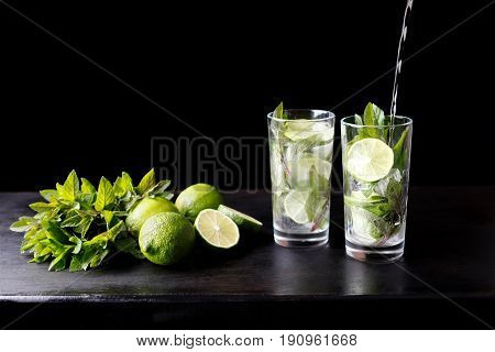 Mojito traditional beach refreshing cocktail alcohol drink in glass bar preparation pouring soda water, lime, mint leaves, sugar, and rum. Dark black background with copy space for text