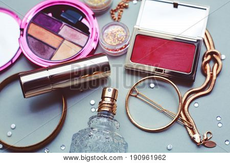 Makeup cosmetics products on grey wooden background. Cosmetics make up artist objects: lipstick eye shadows eyeliner concealer powder tools for make-up