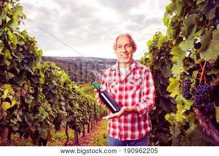winemaker standing by his vineyard, holding bottle of wine