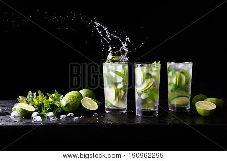 Three glasses of refreshing Mojito rum alcohol cocktail on the bar, splashes in a glass. Party cocktail. Lime, ice and mint on the table. Black background. Copy space for text.