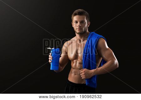 Studio shot of a young handsome shirtless bodybuilder with hot sexy body posing on black background showing off his ripped torso holding bottle of water and towel.