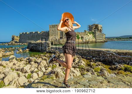 Happy attractive tourist vacation woman with sun hat enjoying on islet of Bourtzi. Methoni Venetian Castle, a medieval fortification, Peloponnese, Greece. Happiness travel holidays lifestyle concept