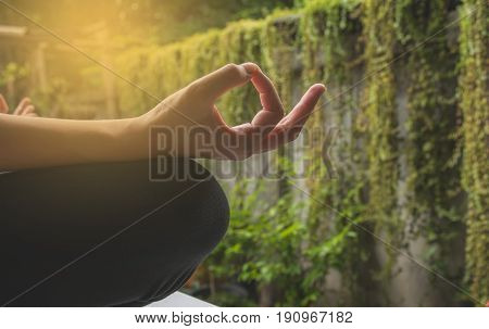 Close-up of feminine and masculine arms and crossed legs during meditation in garden.