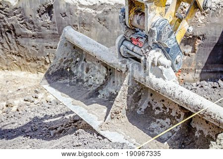Excavator's tool bucket blade on the ground close up shoot