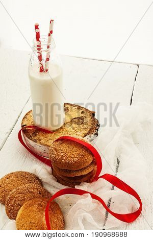 A Stack Of Round Shortbread Cookies And A Bottle Of Milk, On A White Rustic Background