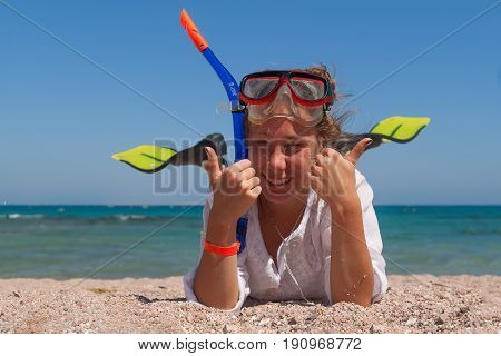 Young Woman In A Mask And Fins For Scuba Diving With His Eyes Closed, Lying On The Sand, Laughing An