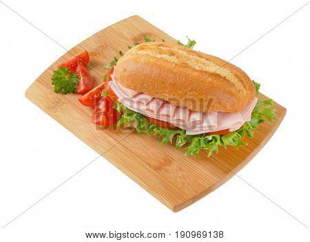 crusty roll sandwich with ham on wooden cutting board