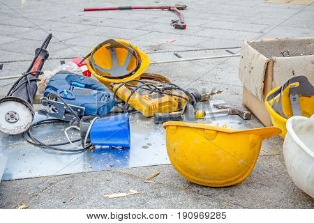 Hardhat and power tool are on the ground with plastic kettle for coffee or tea.
