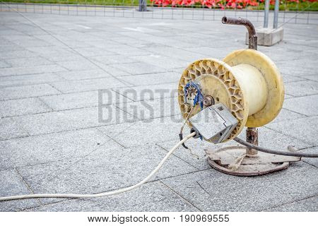 Connection to extension cord with reel is providing electrical energy to construction site.