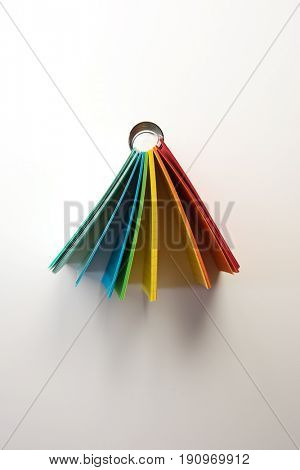 Comes in colors. A colorful memo pad or small note tablet, shot from the side, isolated on natural white background.