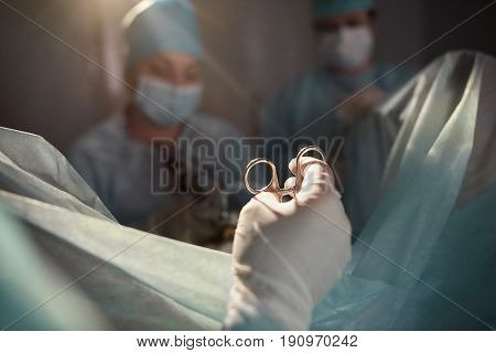 Cropped close up of a surgical instrument in the hands of a surgeon performing operation with his medical team healthcare emergency ambulance concept.