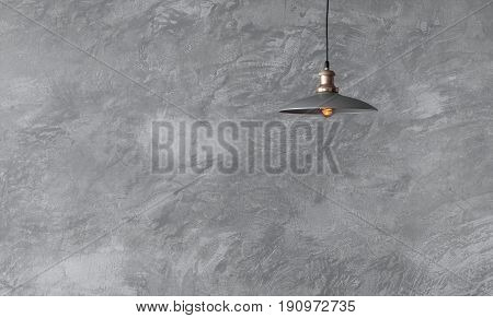 Industrial pendant lamps against rough wall with gray cement plaster. Edison light bulbs in loft style.