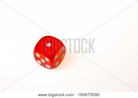 A single red die showing a one on the upper face isolated against a white background