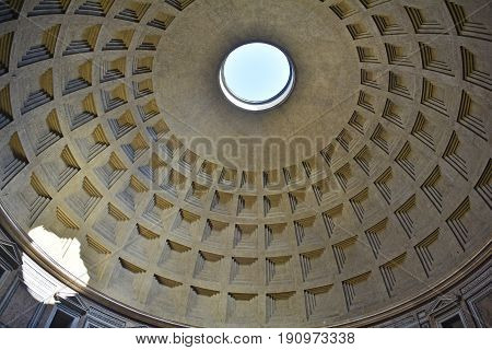 The landmark Pantheon in Rome Italy. Originally a temple and now a church it has a coffered concrete dome which has a central opening or oculus to the sky.