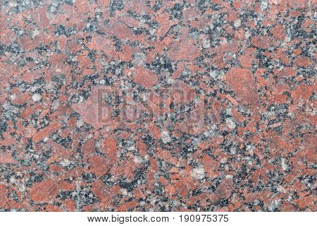 Granite polished slab of brown with gray dark and light spots and streaks and cracks between them. Red-brown spots of different shapes mostly oval.