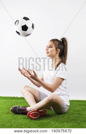 Teen girl juggling soccer ball with her hands. Gray background.