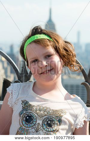 View of a Beautiful young girl on observation deck overlooking the lower Manhattan New York City skyline