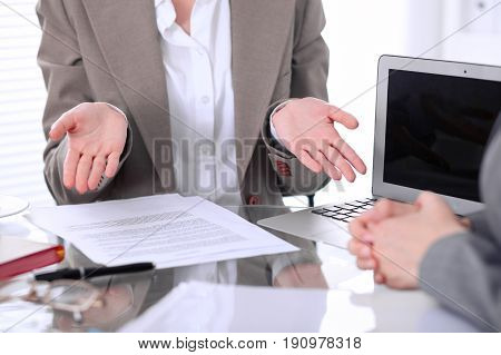 Group of business people or lawyers at meeting discussing contract papers. Woman showing that she do not understand how it happen or what to do.