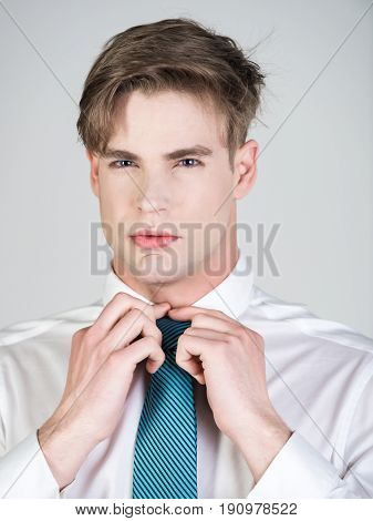 Groom Tying A Striped Tie In White Shirt