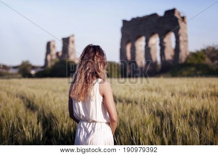 Girl in white dress shrugging while looking at an ancient Roman aqueduct. The scene takes place in a cultivated field of wheat.