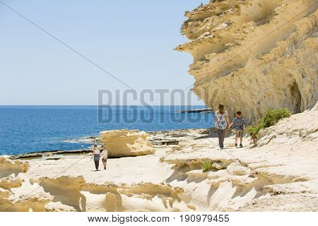 Malta rocky coast, family walk along the beach