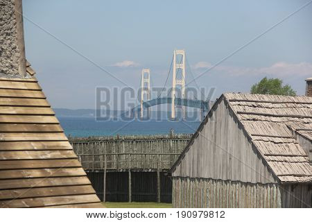 The walls of Fort michilimackinac on the Straits of Mackinac, with the Mackinac Bridge in the background.  Michigan, USA