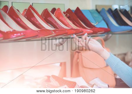 customer hand at shopping showcase with female footwear or colorful shoes and shop assistant beauty and fashion