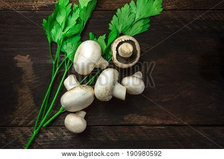 An overhead photo of fresh white mushrooms with green parsley on a dark rustic texture with a place for text