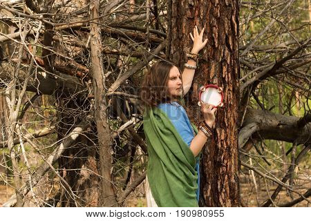 A Young Girl With An Ethnic Makeup And A Tambourine In The Forest. Boho Hippie Style Fashion Portrai