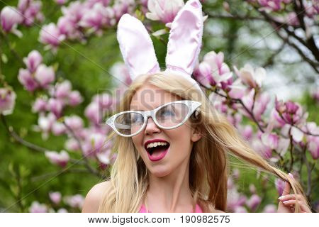 Spring easter surprised woman or pretty girl with funny glasses bunny ears and open mouth with long blond hair at blossoming tree with magnolia flowers in park on sunny day on floral environment.