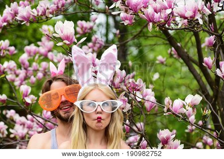 couple in love making fish lips face grimace in glasses and rosy bunny ears. Pretty girl or cute woman and handsome man or macho on blossoming floral environment. Spring. Easter celebration