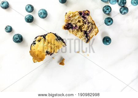 An overhead photo of two halves of a blueberry muffin with fresh blueberries and crumbs scattered around, with a place for text