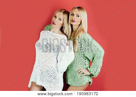 twins. Two pretty girls or cute women twins fashionable models with blond long hair stylish makeup and sexy knitted sweaters posing on red background. Female fashion and beauty