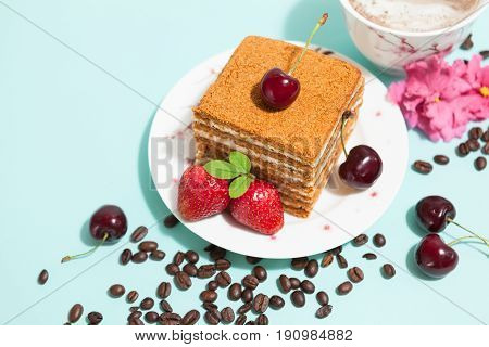 Tasty cake on the white plate and cup of coffee with cream, decorated with flowers, coffee beans, strawberries and ripe cherry on the mint background with place for text, top close up perspective view