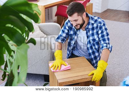Mid shot of good-looking bachelor in gloves mopping coffee table