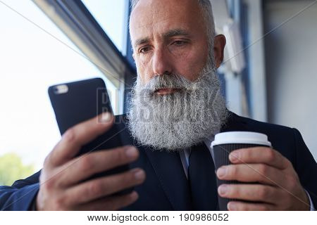 Close-up of pokerfaced man age of 50-60 holding cup of coffee and surfing in phone